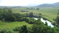 Aerial shot of a river flowing through meadows video