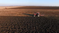 Aerial shot of a tractor plowing a field video