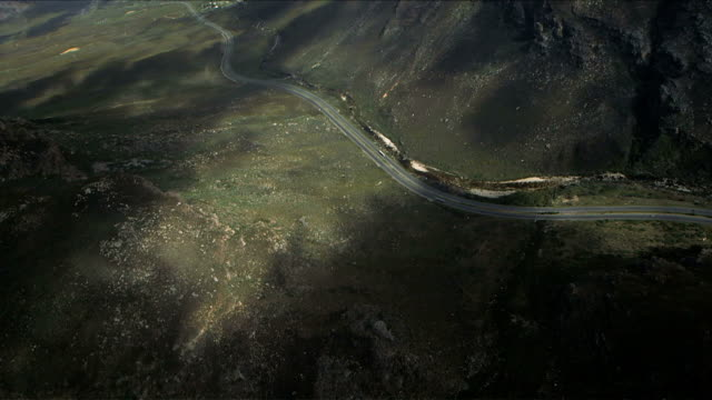 Aerial shot of cars travelling along South African mountain pass, Du Toit's Kloof, Western Cape. Daytime, partly cloudy. video