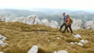 Aerial shot of couple hiking the mountain top video