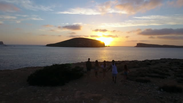 Aerial Shot Of Friends On Cliffs Watching Sun Set Over Sea video