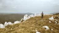 Aerial shot of hiker walking on the mountain ridge video
