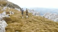 Aerial shot of hiking couple walking the mountain ridge video