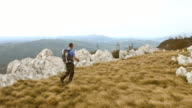 Aerial shot of man hiking on the mountain ridge. video