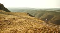 Aerial shot of mountain biker progressing up the ridge video