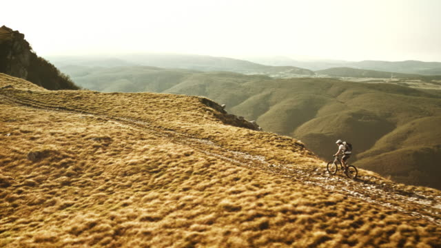 Aerial shot of mountain biker progressing up the ridge video