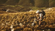 Aerial shot of mountain biker riding up the ridge video