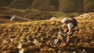 Aerial shot of mountain biker riding up the ridge video