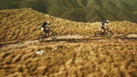 Aerial shot of mountain bikers riding on plateau top video
