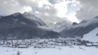 Aerial shot of snowy alpine valley below the mountain tops video