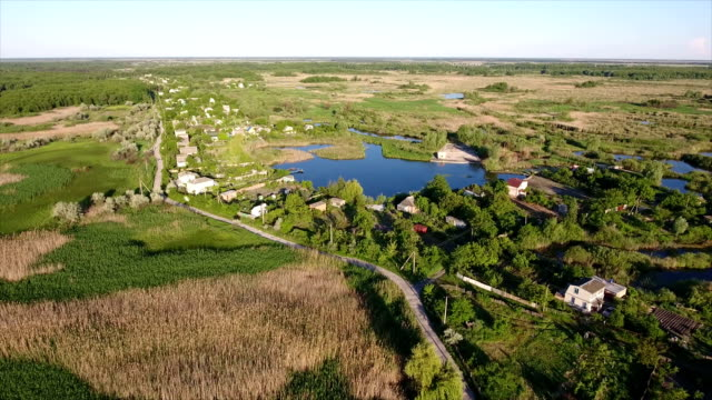 Aerial shot of summer cottages, splendidl lake and reedbeds in Ukraine in summer video