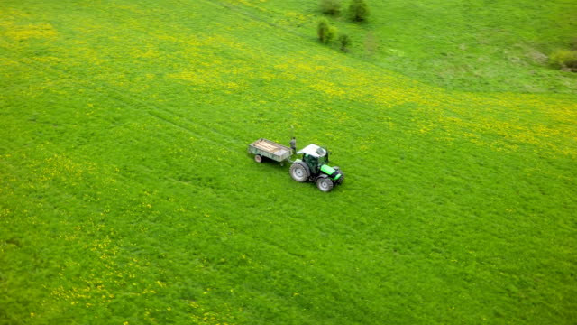 Aerial shot of Traktor on green Pasture video