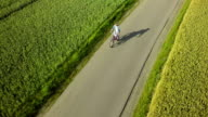 Aerial shot of women riding bicycle on country road video