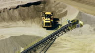 Aerial shot tractor working at rock quarry, zoom ou video
