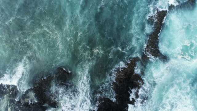 Aerial Slow Motion Shot Of Waves Rushing Towards Rocky Shore video
