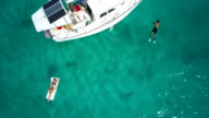 aerial slow motion video of people relaxing on a sailboat video