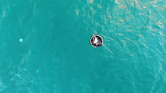 Aerial Survey A fisherman swims in a boat by sea video