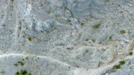 Aerial: tilted down while moving over edge of vertical mountain cliff video