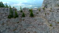 Aerial: tilting down while moving over edge of vertical mountain cliff video