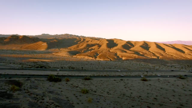 Aerial tracking shot along a lonely highway in desert at sunset. video