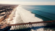 Aerial tracking shot of a beautiful sunrise sparkling off the ocean as the pier seems to go on forever into the blue abyss. video