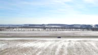 Aerial truck driving down backroad around snow covered farm land video