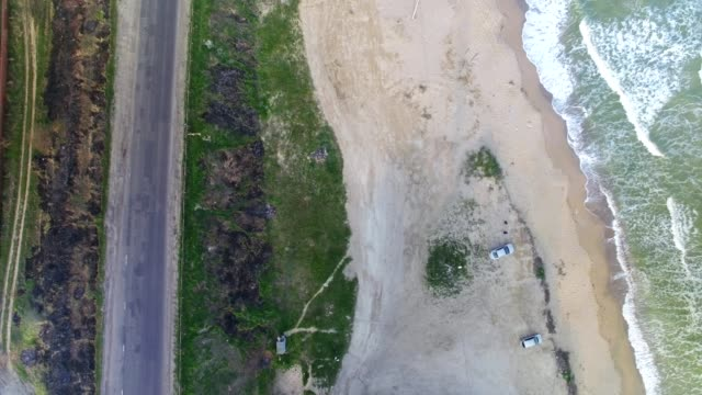 Aerial upside-down view of sea coast and cars on the beach video