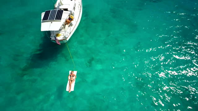 aerial video of a sloop anchored in the Caribbean bay video