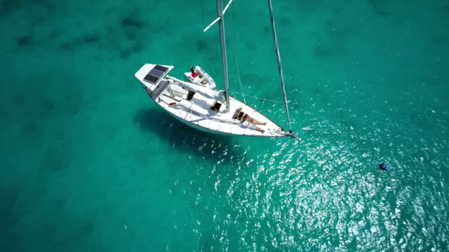 aerial video of honeymoon couple relaxing on a luxury sailboat video