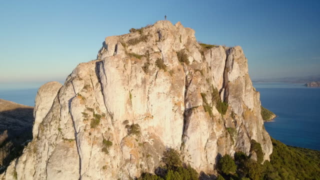 Aerial video shot by a drone of a man on the top of the mountain. Emerald coast, Sardinia, Italy. video
