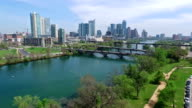 Aerial View Austin Texas Skyline Colorado River Fun Spring water activities going down low near trees with joggers on hike and bike trail video