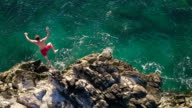 Aerial View Cliff Jumping into Blue Ocean. Summer Action Sports Lifestyle. Young Man Jumps off Cliff in Slow Motion. video