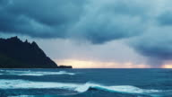 Aerial view flying over ocean reef and waves into dramatic sunset storm on the north shore of Kauai video