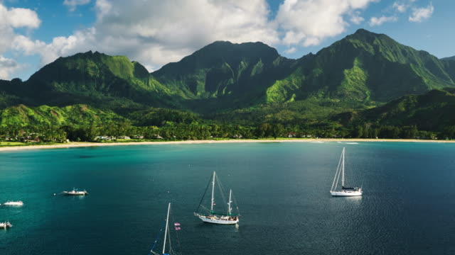 Aerial view flying over sail boats in Hanalei Bay towards beautiful green mou video