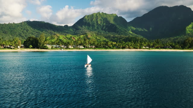 Aerial view flying over traditional Hawaiian sail boat in tropical blue lagoon towards beautiful green mountains video