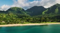 Aerial view flying over tropical blue ocean towards beautiful green mountains video