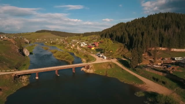 aerial view from a height on the river and village near a forest video
