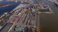 Aerial view from helicopter fly above colorful cargo containers in seaport. Height. Sunny. Water video