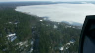 Aerial view from helicopter fly above green forest and frozen lake. Camera inside. Landscape. Ice video