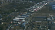Aerial view from helicopter fly above green trees, garages in countryside. Height. Sunny day video