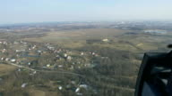 Aerial view from helicopter fly above houses in countryside, field. Height. Sunny day. Landscape video