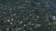 Aerial view from helicopter fly above houses in countryside. Green trees. Height. Sunny day video