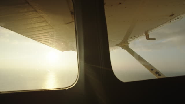 POV aerial view from inside small plane at sunrise over ocean video