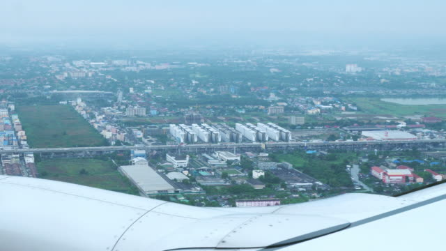 aerial view in the air over the city form air plane cabin window. video