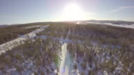Aerial view of a country winter road through the forest  in a beautiful winter day - Harads, Boden Municipality, Norrbotten,Sweden video