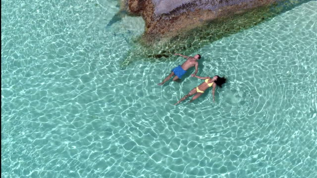 Aerial view of a couple floating in the water at a tropical beach video