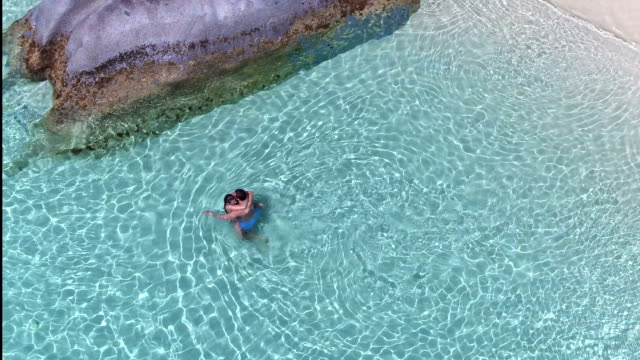 Aerial view of a couple hugging in the water at a tropical beach video