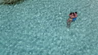 Aerial view of a couple relaxing in the water at a tropical beach video