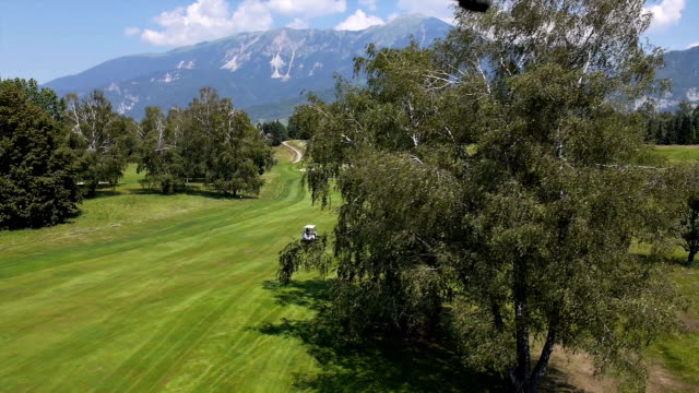 Aerial: view of a golf course. Golfer rides in golf cart video