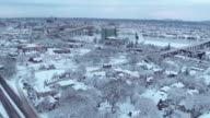 Aerial view of a gondola crossing over a snow covered city video